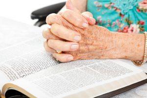 senior woman praying with bible