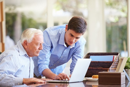 31067242 - teenage grandson helping grandfather with laptop