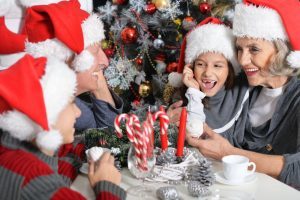 65629477 - portrait of happy grandparents with their grandchildren in santa hats celebrating christmas at home