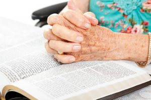 senior woman praying with bible
