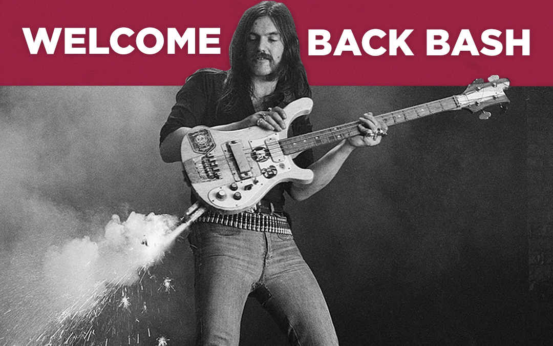 """Old black and white photo of a rock guitarist holding an electric guitar with fireworks shooting out of it. Text above it reads, """"Welcome back bash."""""""